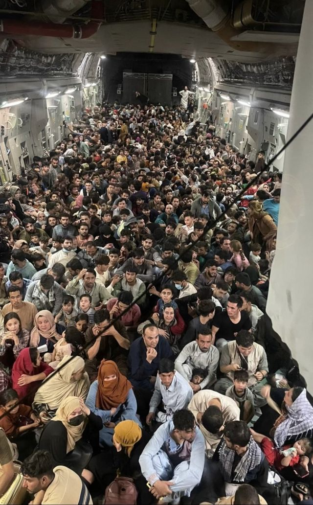 Image provided by US Air Mobility Command shows hundreds of Afghans fleeing Kabul aboard a US C-17 cargo plane, August 15, 2021.