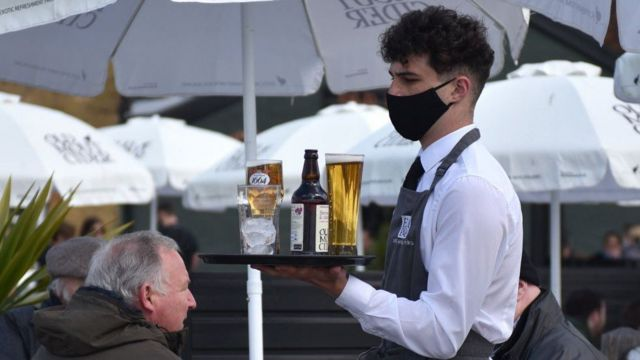 Masked employee with a plate of drinks at the restaurant