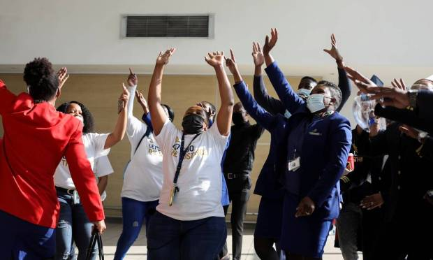 Workers celebrate as a South African Airways (SAA) plane prepares to take off at Tambo International Airport in Johannesburg, South Africa, after a year-long layover because the national airline ran out of money.  Photo: SIPHIWE SIBEKO / REUTERS