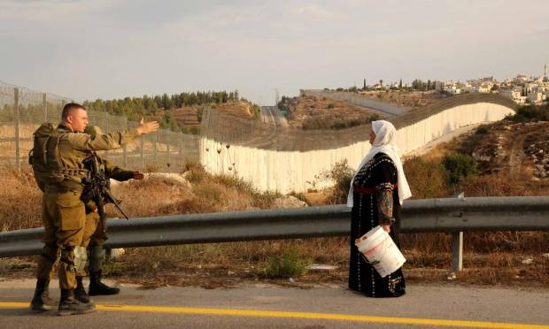 A Palestinian woman talks to an IDF military man in his olive fields on the other side of the Israeli separation wall, after obtaining special Israeli permission to pick olive trees in Hebron, West Bank, Photo: Hazem Bader/AFP