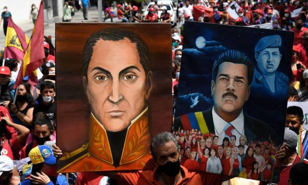 A supporter of Venezuelan President Nicolas Maduro displays selfies of himself and Venezuelan liberator hero Simon Bolivar during a rally to commemorate the Day of Resistance of Indigenous Peoples in Caracas. Photo: FEDRICO PARRA / AFP