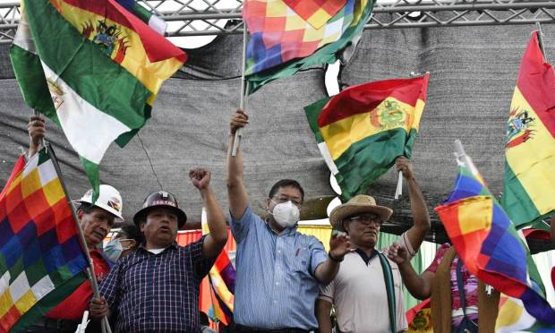 Bolivian President Luis Arres, wearing a mask, waves the Wipala flag - representing the indigenous peoples of the Andes - during a pro-government rally in Santa Cruz, Bolivia. Photo: AIZAR RALDES / AFP